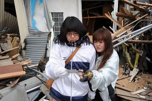OFUNATO, Japan (March 15, 2011) - A mother and daughter pause for reflection as they find a family photo amid the wreckage of their home.