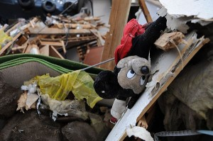 A Mickey Mouse doll lies in tatters among rubble and debris